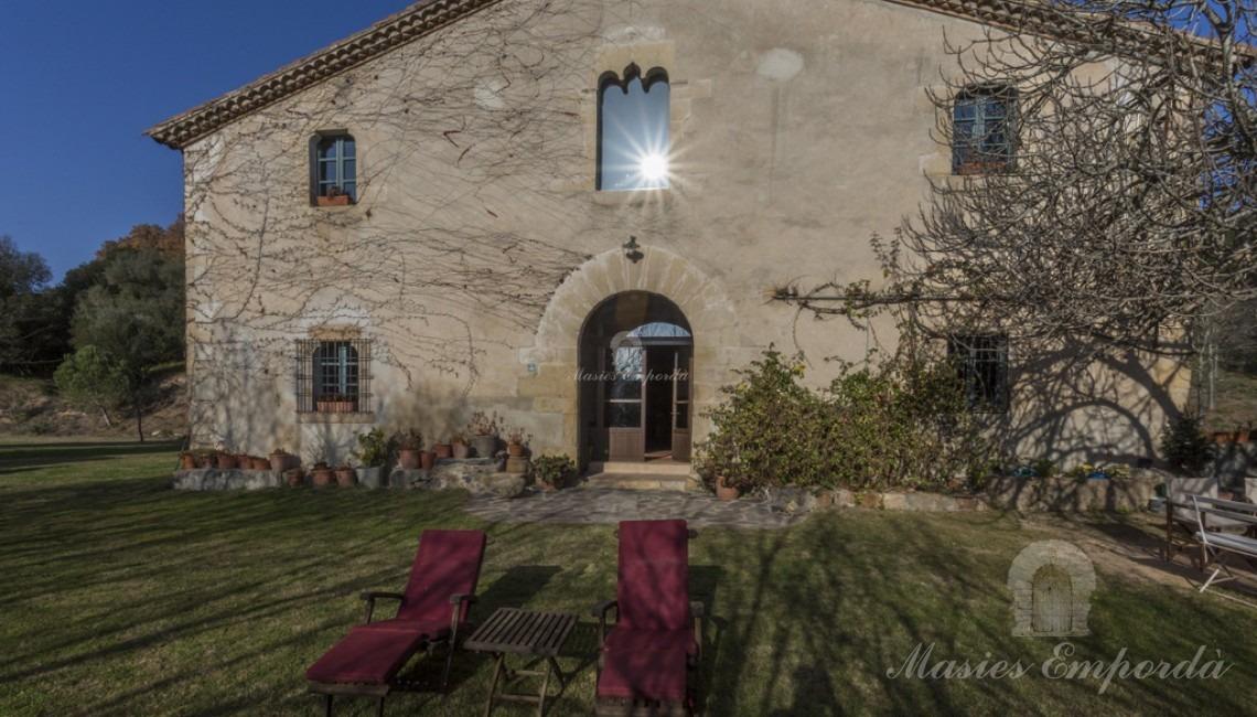 Vista de la facha de masía y el jardín al medio día reflejando el sol en la cristalera de la ventana gótica de la fachada