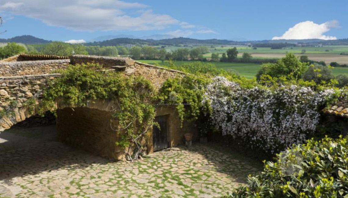 Vista del puente arcado de piedra que soporta terrada desde la perspectiva inversa a la entrada a la masía con espectaculares vistas a los campos de la propiedad y del Baix Empordà
