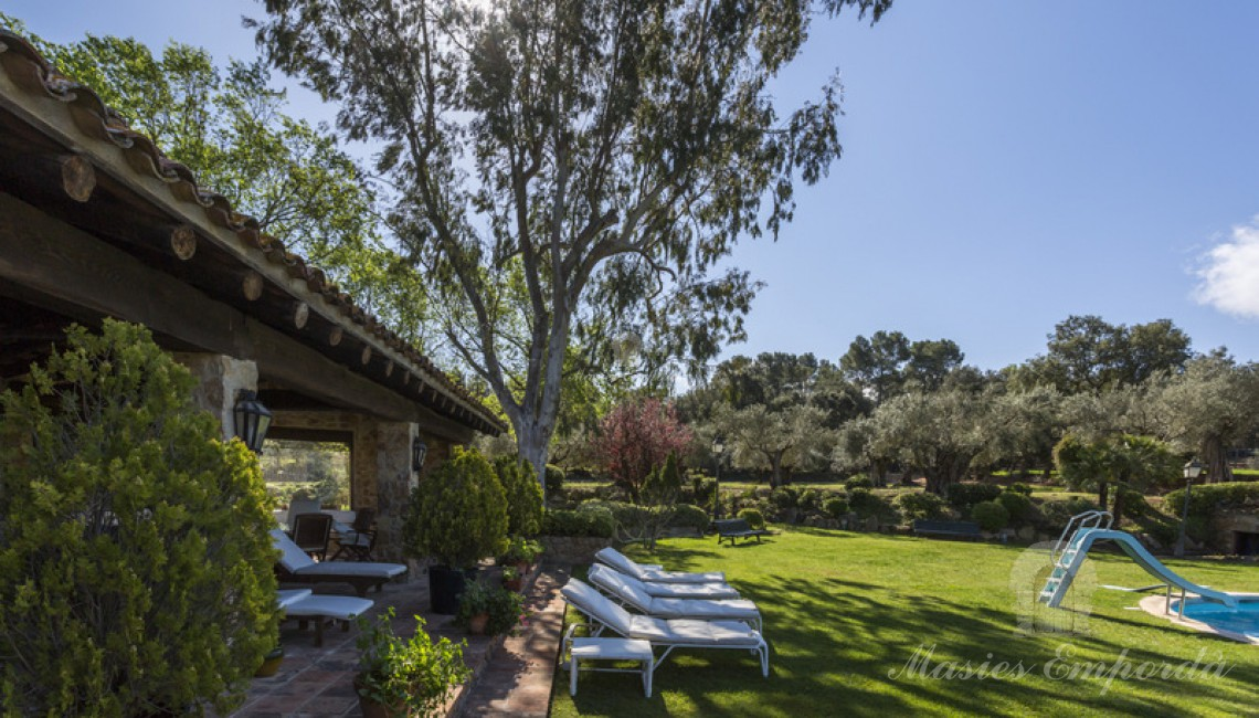 Vista del porche abierto con parte del jardin de la piscina