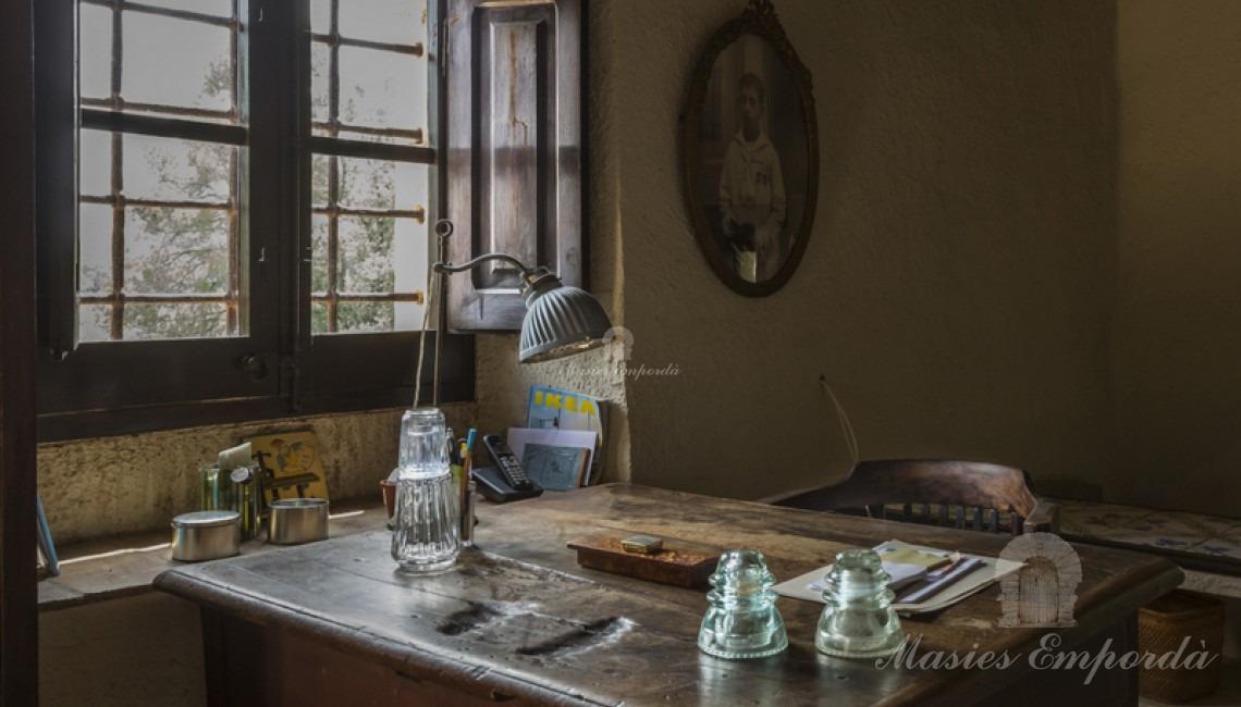 Mesa de trabajo en madera de una de las estancias de la casa junto a ventanal.