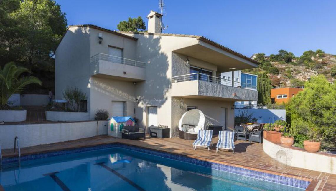 La casa desde la piscina, donde se aprecia la terraza solárium y el jardín