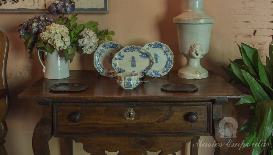Detail of furniture on the upper floor with Italian porcelain dishes and vase.