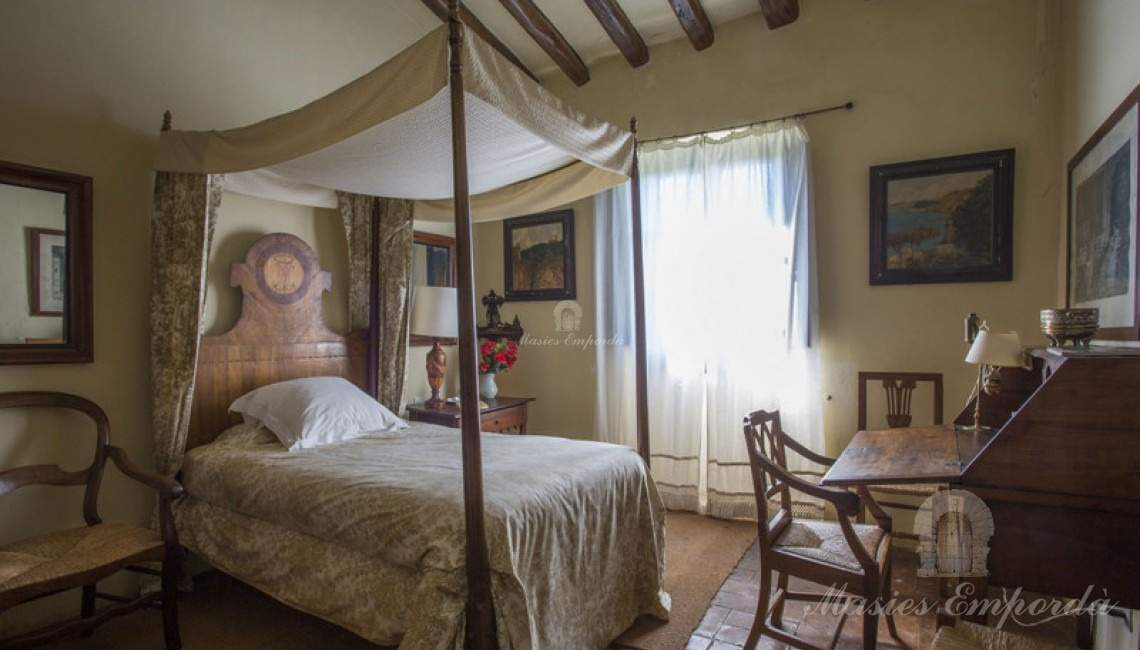 Top floor room with double bed with canopy and wooden secretary.