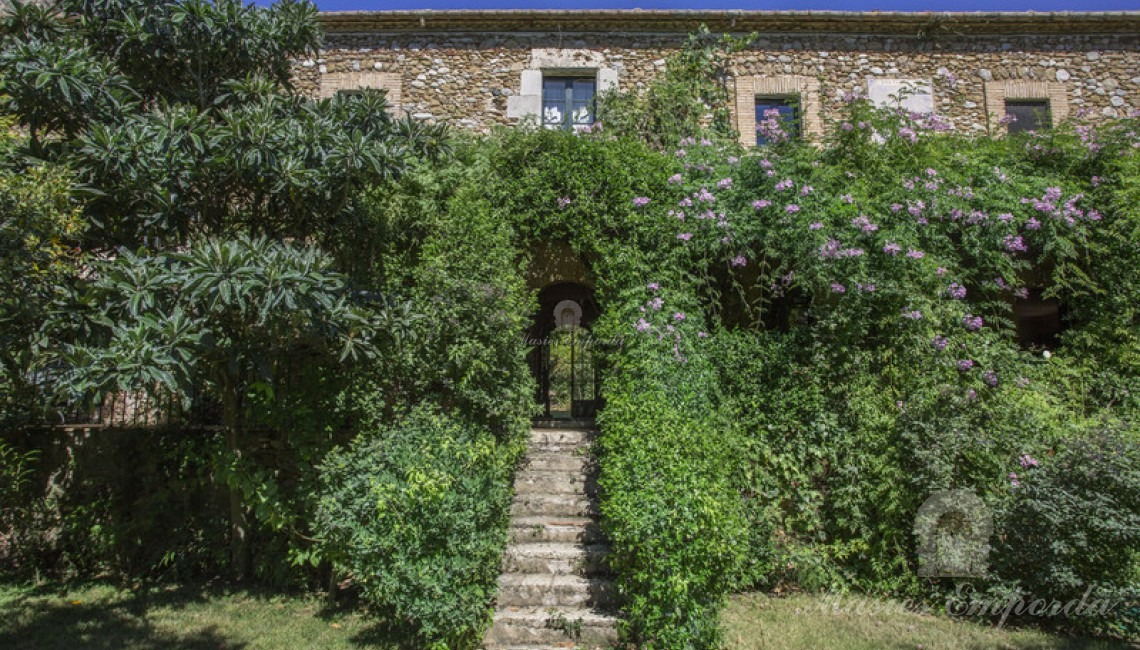 Main facade of the farmhouse ambushed by the lush garden surrounding the property with access stairs to them from the garden.