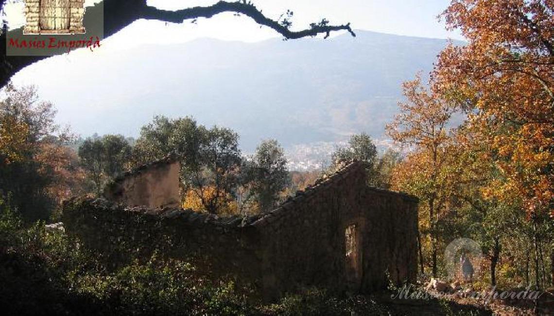 Vista de la estructura en piedra de las paredes de la casa sin cubierta ni bigas de soporte.