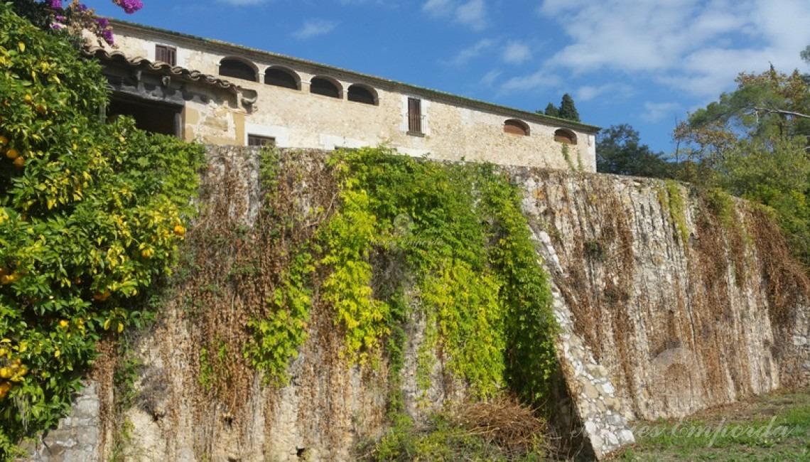 Muralla con contrafuertes parte sur de la masía que cobija en su interior parte del jardín que rodea la casa