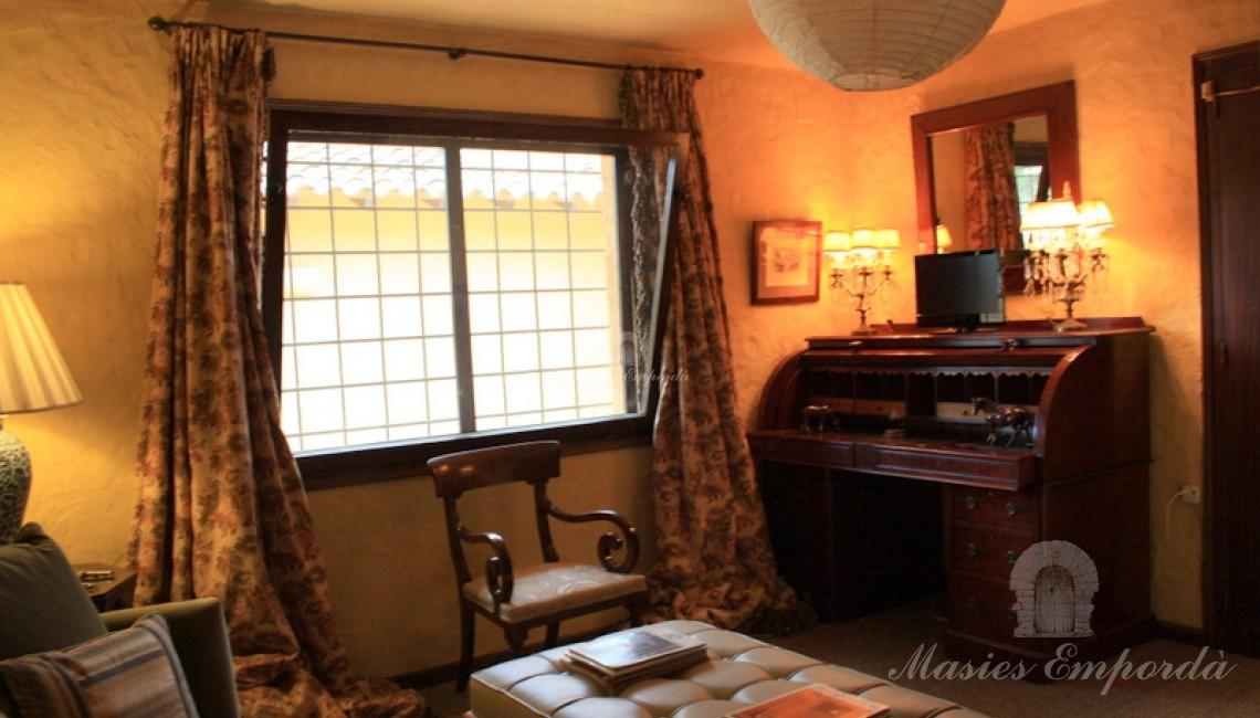 Una de la habitaciones de la casa con despacho secreter de madera como detalle