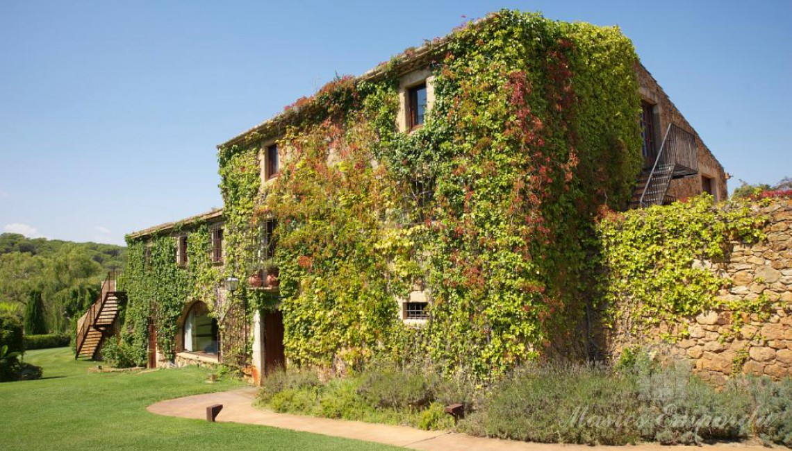 Side view of the farmhouse located in the town of Pals in the Baix Empordà and the garden on the inside of this where the vine can be seen covering the structure of the house as a whole.