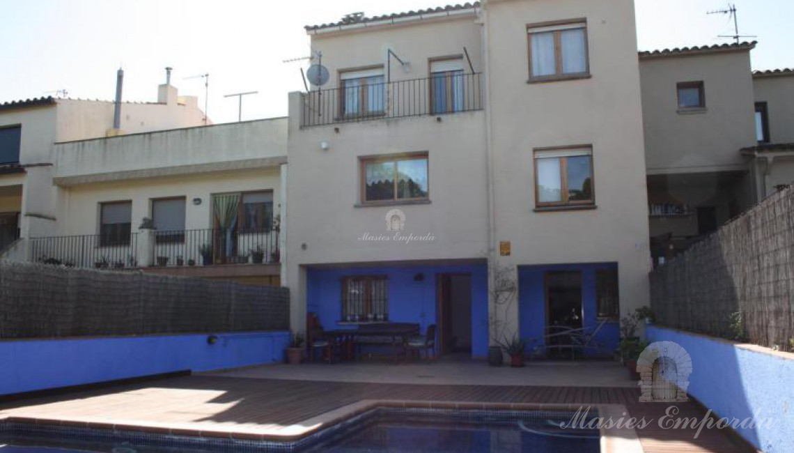 Vista de la piscina y de la casa al fondo de la imagen