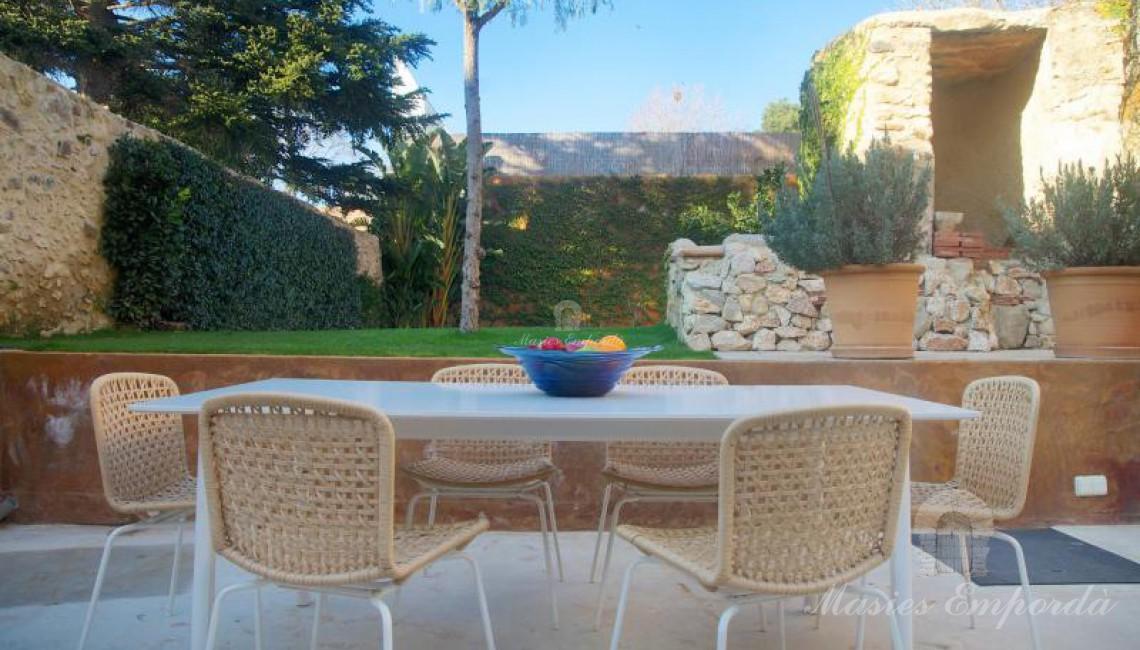 Vista del comedor de verano con el pozo de piedra de la casa y el jardín en segundo plano