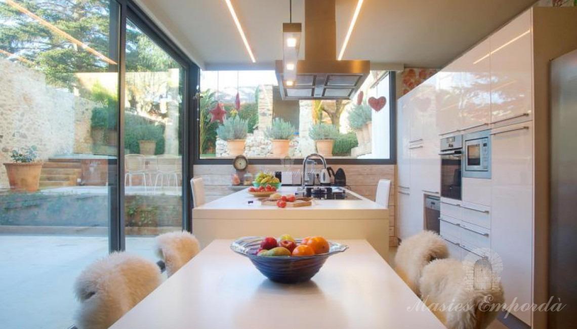 Vista de la mesa del comedor y la cocina con la vista del jardín a través de la espectacular vidriera