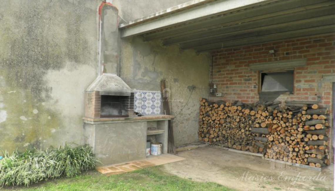 Detalle de la barbacoa y leñera del porche adjunto a la casa