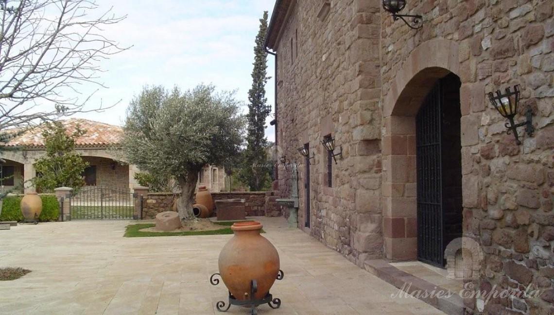 Fachada de la masía en su vertiente sur-oeste con salida al jardín y terrazas.