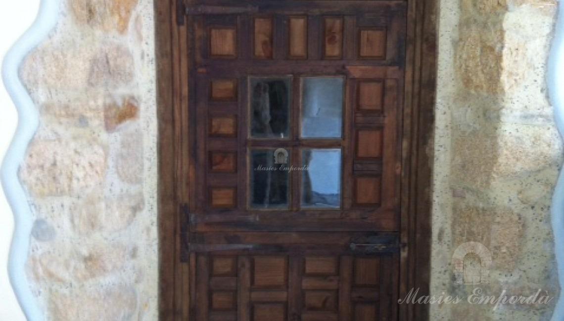 Detalle de una puerta de madera labrada con ventanuco acabado en cuatro cristales enmarcados en madera