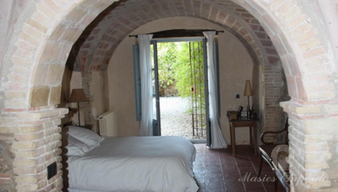 Suite principal de la masía con entrada con arco de medio punto de tocho macizo y remate de la bóveda en crucería de distribuidor de zona de noche de la casa.