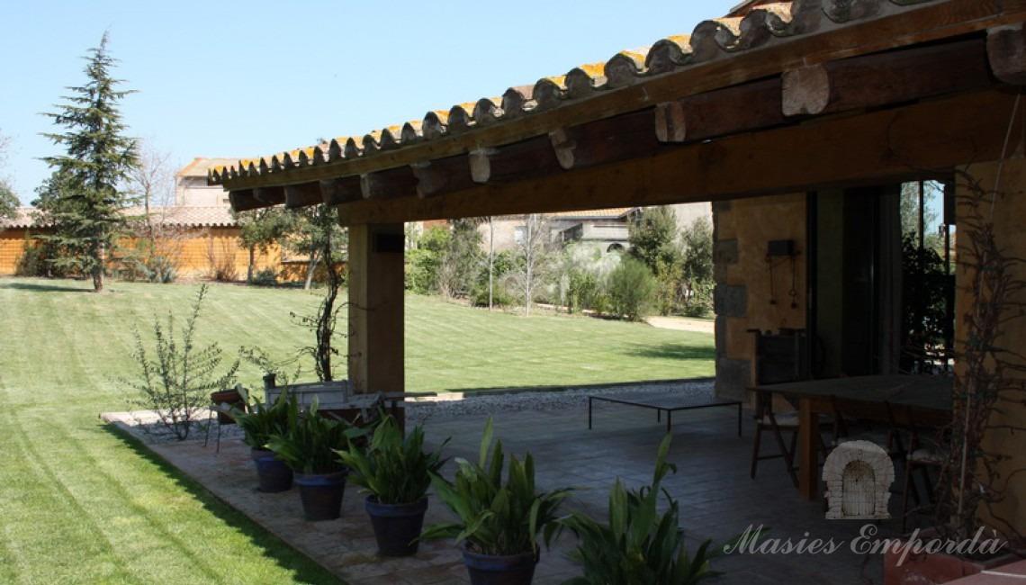 Porche con el comedor de verano adjunto a la cocina ubicado en terraza con vistas al jardín