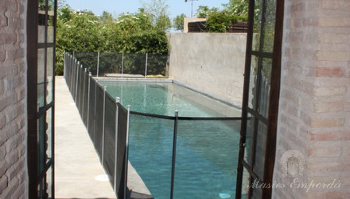 Vista de la piscina y el jardín desde el pabellón de verano
