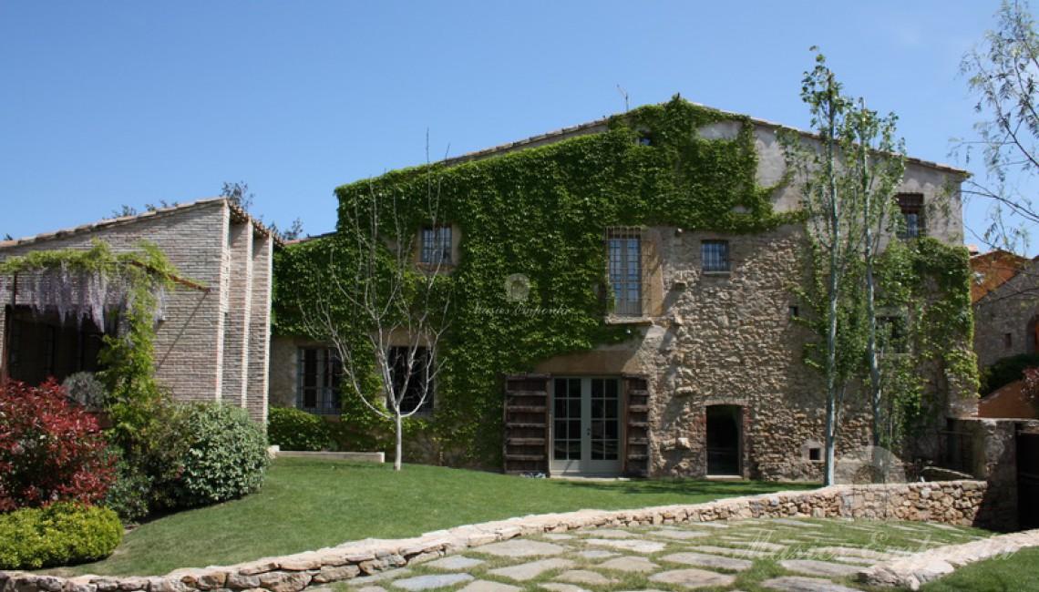 Fachada de piedra de la masía con la yedra trepadora en un lateral y el pabellón de verano con pérgola metálica en el frontal de este