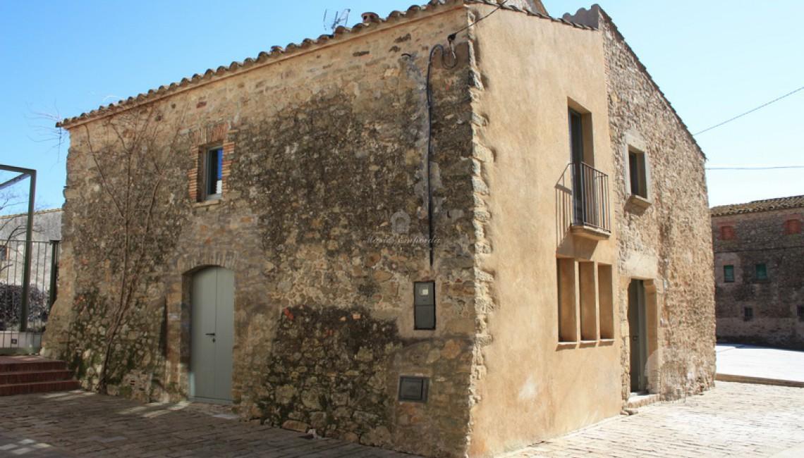 Vista de la fachada y el lateral de la casa de pueblo con entrada de vehículos en el lateral de esta