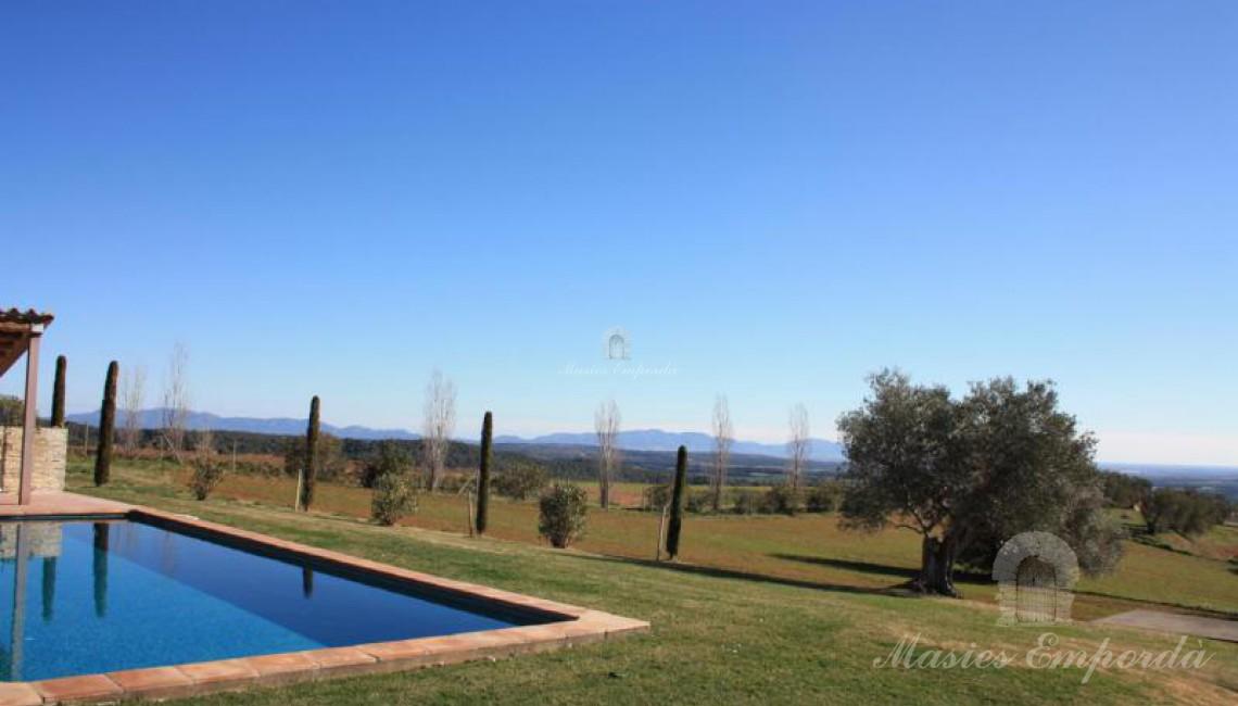 Vista de la piscina y el porche de esta con vista a la comarca y al mar al fondo de la imagen