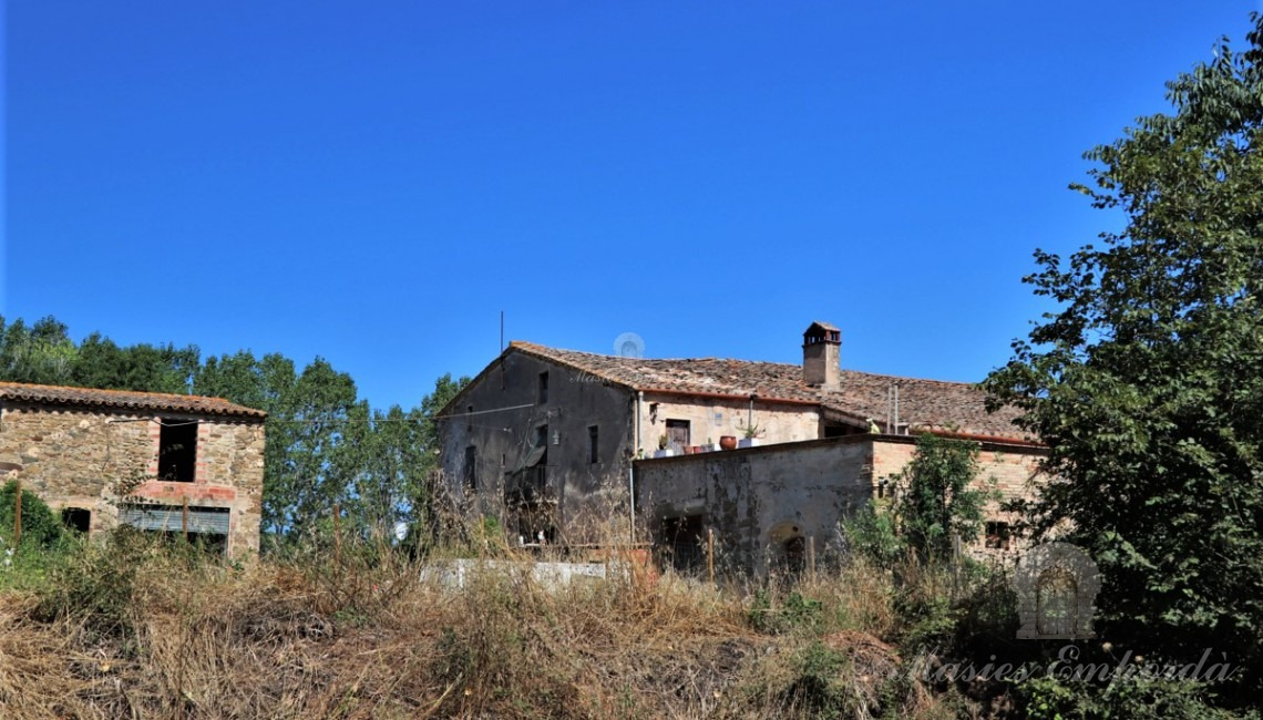 View of the architectural set of the buildings of the farmhouse surrounded by the farm fields of the property