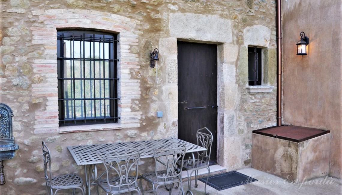 Detalle de la terraza de la entrada de la casa, con la barbacoa y comedor de verano