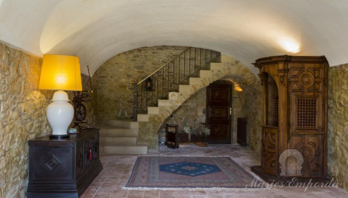 Entrance hall to the farmhouse with the staircase leading to the upper floors and the main living room.