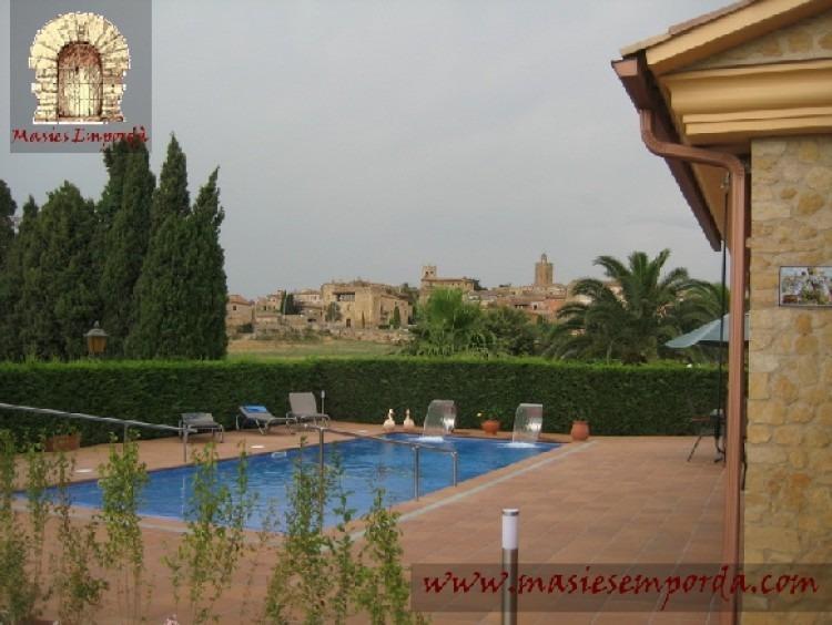 Vista de la casa, la piscina y el jardín con el pueblo al fondo de la imagen