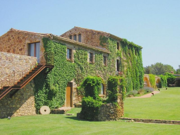 General view of the farmhouse for sale located in the town of Pals in the Baix Empordà and the garden on the inside of this where the vine can be seen covering the structure of the house as a whole.