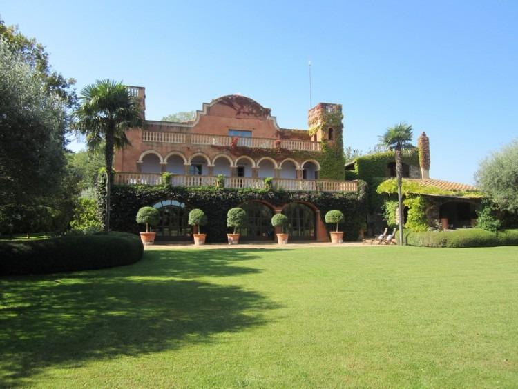 Fachada sur de la masía donde se aprecia el estilo colonial de esta parte de la casa rodeada de este cuidado jardín