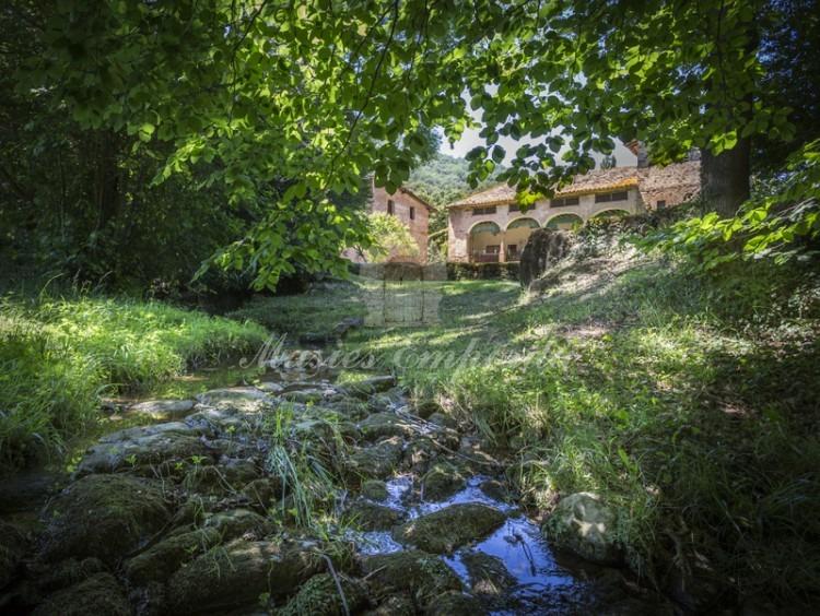 Desde el rio que fluye por la propiedad vista el conjunto constructivo de la masía.