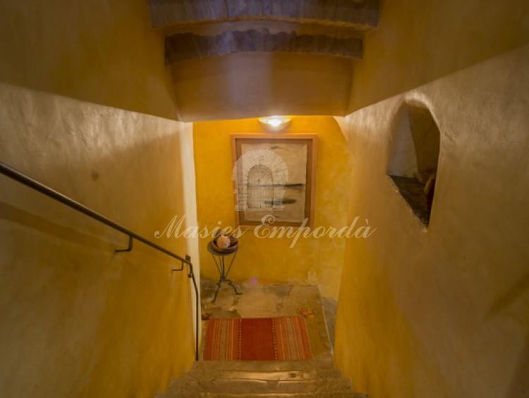Detalle de escalera interior de piedra de la casa que da acceso a las plantas, con fino pasa manos de forja
