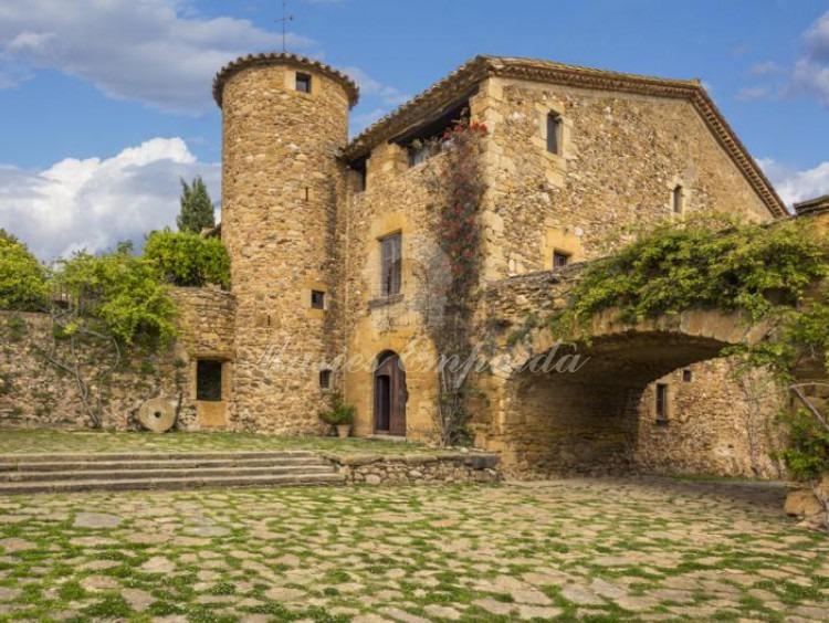 Vista del interior del patio que parece de la entrada a la masía con torre circular de defensa y puente arcado de piedra que soporta terrada con espectaculares vistas a los campos de la propiedad