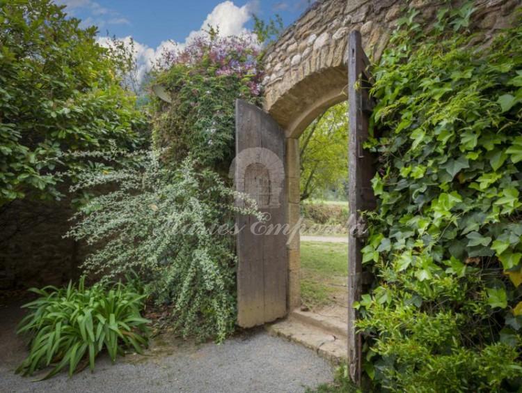 Portón de madera de entrada al partió de la masía con el jardín en flor aun lado del portón y una exuberante enredadera en el otro