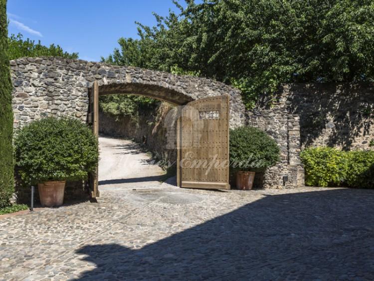 Muro de piedra y portón de madera que da acceso a la propiedad