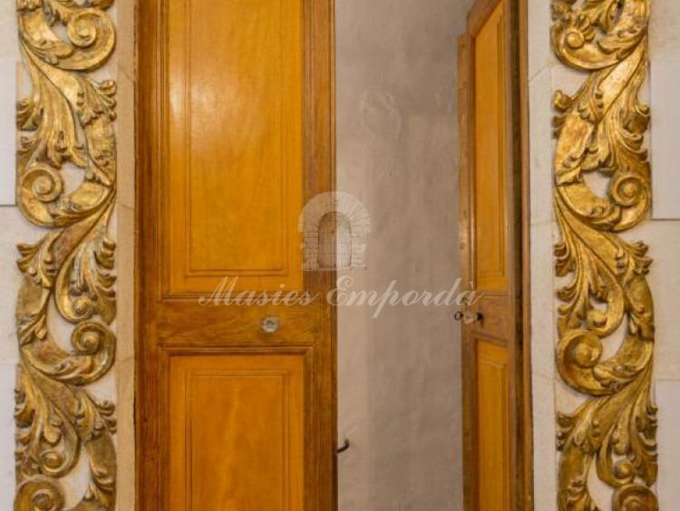 Detalle de la puerta de acceso a unos de las salones con dintel en piedra tallada y detalles de policromados en laterales de los pilares y corona del dintel.