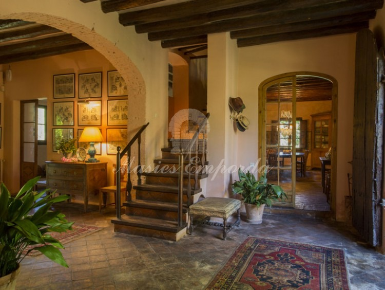 Entrance hall to the house with the access staircase to the floor on one side with central arch for loading and wooden beams seen.