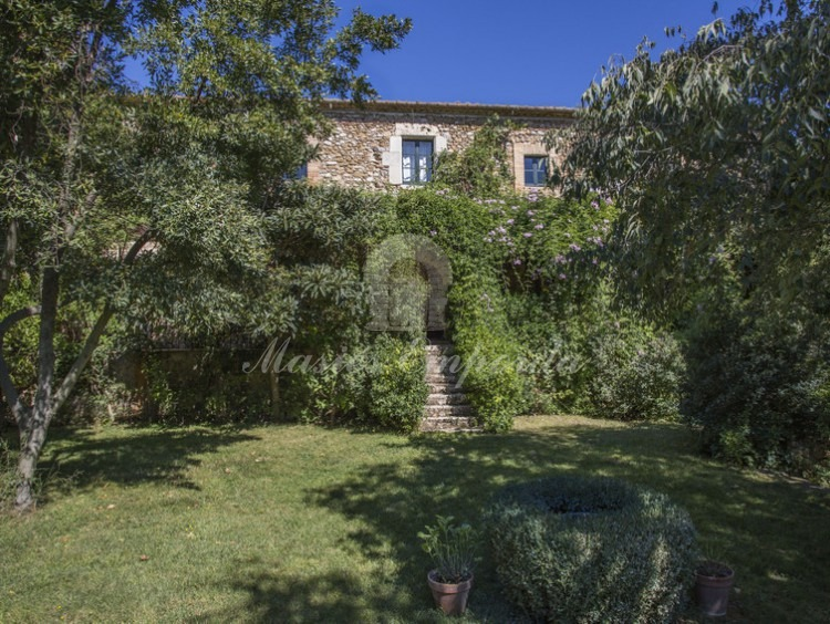 Main facade of the farmhouse ambushed by the lush garden surrounding the property with access stairs to them from the garden and pool.
