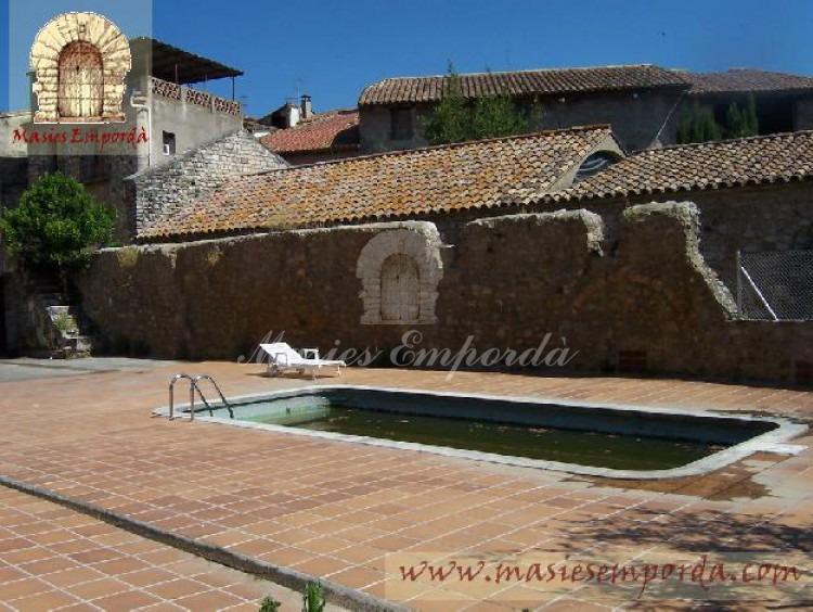 Vista de la piscina en terraza con restos de fortificación antigua y de la casa da una vistosidad poco común