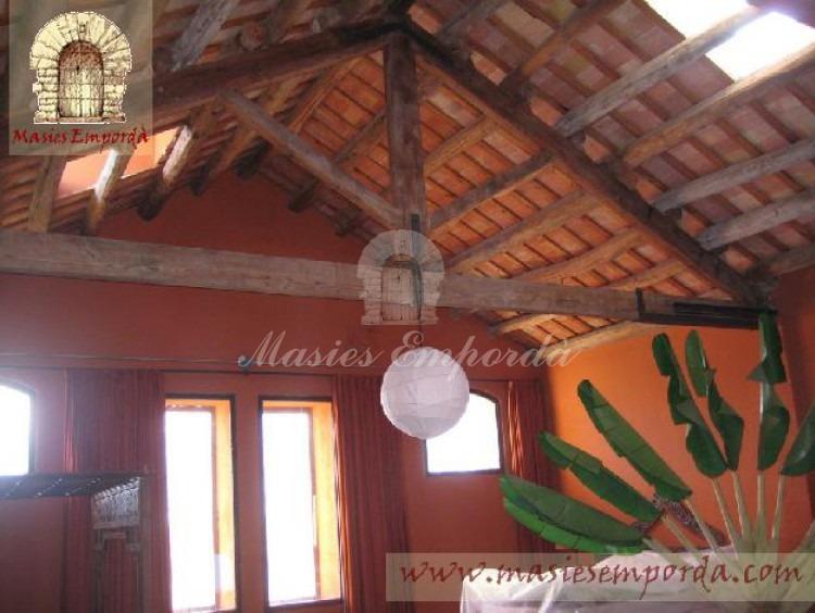 Salón de la planta con cubierta dos aguas y vigas de madera vistas