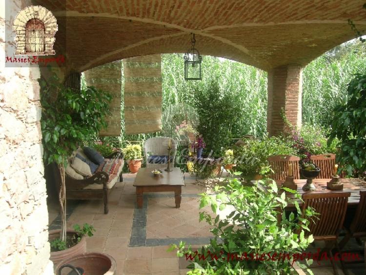 Porche de la casa con vistas al jardín y la piscina con un amplio arco de crucería de tocho macizo que da una vistosidad al mismo extraordinaria
