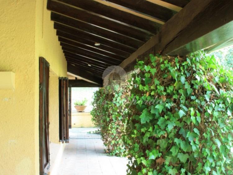 Vista del porche lateral corroído en fachada con vigas de madera que lo soportan