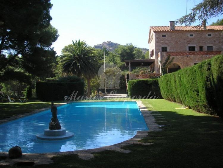 Vista de la piscina con escultura en piedra caliza en su interior y de fondo la casa y los jardines de la casa