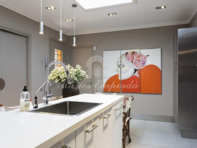 Amplia y luminosa cocina de la casa con isla de trabajo central con el extractor de humos, fogones y fregaderos integrados en ella.