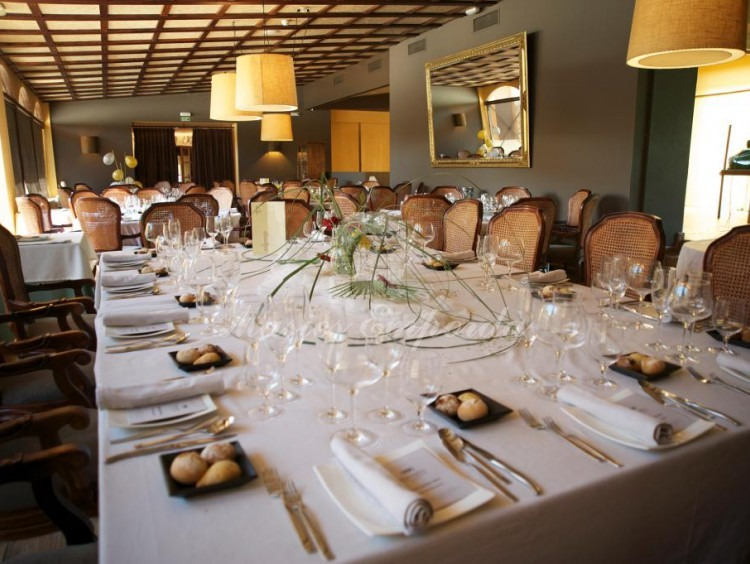 General view of the dining room with details of one of the tables decorated and set for an event with glassware and cutlery arranged.