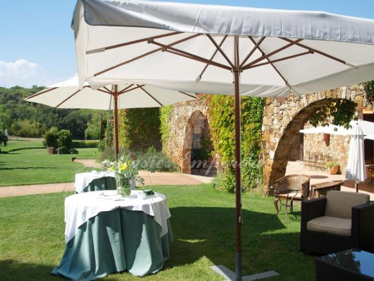 View of the garden with the stone arches that separate the garden terrace with several service tables for snacks and sunshades.