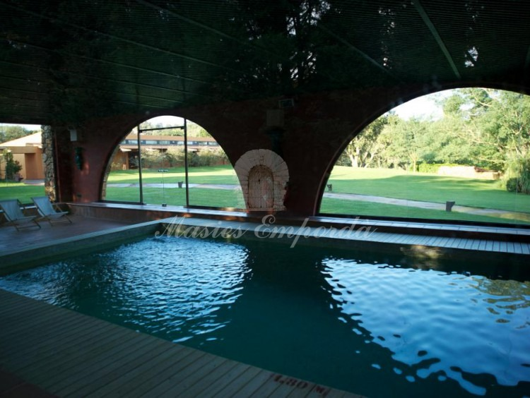 View of the interior of the indoor pool and heated with stone arches that show part of the garden of the property
