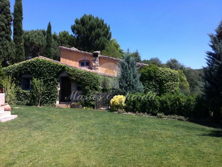 Vista lateral de la entrada y del cercado del jardín de la casa de invitados con la yedra que cubre las paredes
