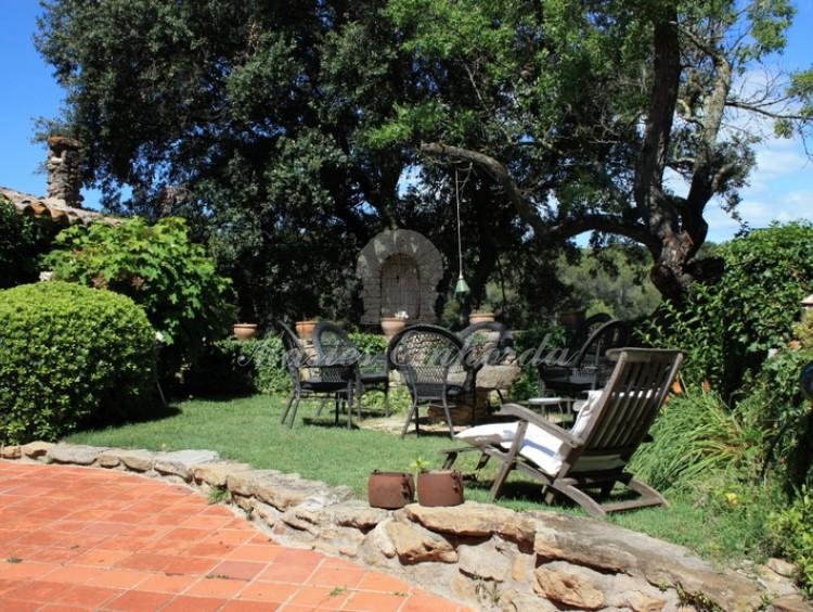 Vista de la entrada a la masía y detalle de conjunto de mesa y sillas de parte del jardín