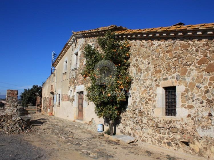 Vista lateral de la fachada de la Masía y el pozo
